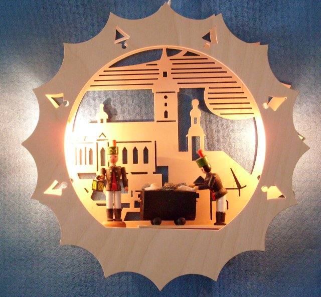 beleuchtetes Fensterbild: Kirche mit Bergleuten
