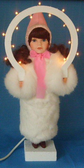 Christkind mit dunklem Haar, rosa Mütze und echtem Kaninchenfell