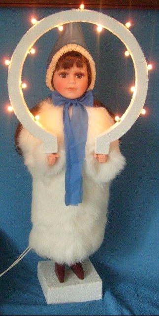 Christkind mit dunklem Haar,blauer Mütze und echtem Kaninchenfell
